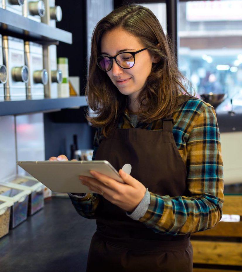 Man in coffee shop looking at orders on screen